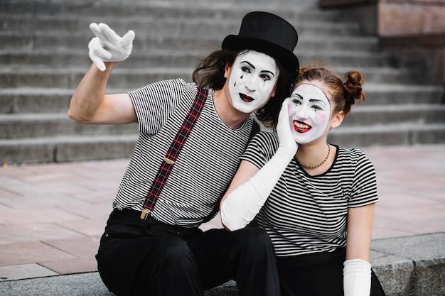 Homme mime montrant quelque chose à l'heureuse femme mime Photo gratuit