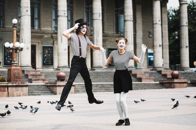 Homme mime tenant la main de la femme mime sautant devant le bâtiment Photo gratuit