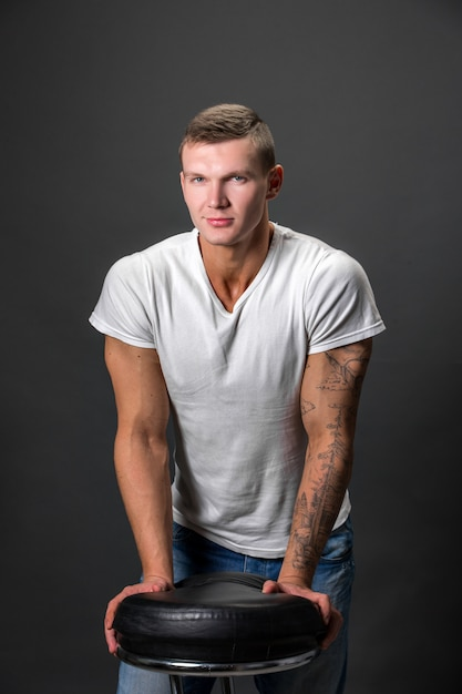 Homme de mode attrayant en regardant la caméra en se tenant debout avec les mains sur une chaise Photo Premium