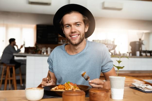 Homme à La Mode Avec Barbe Apaisant La Faim Tout En Mangeant Seul Au Restaurant Moderne Par Une Journée Ensoleillée, Manger Un Repas Avec Un Couteau Et Une Fourchette Photo gratuit
