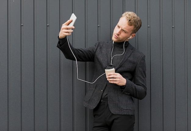 Homme à la mode avec café prenant un selfie Photo gratuit