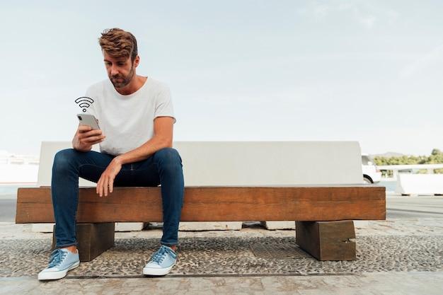 Homme moderne en parcourant le téléphone sur un banc Photo gratuit