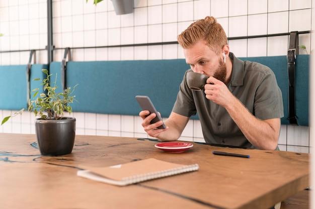 Homme Moderne Regardant Son Téléphone Photo gratuit