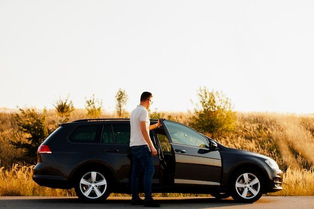 Homme montant dans la voiture Photo gratuit