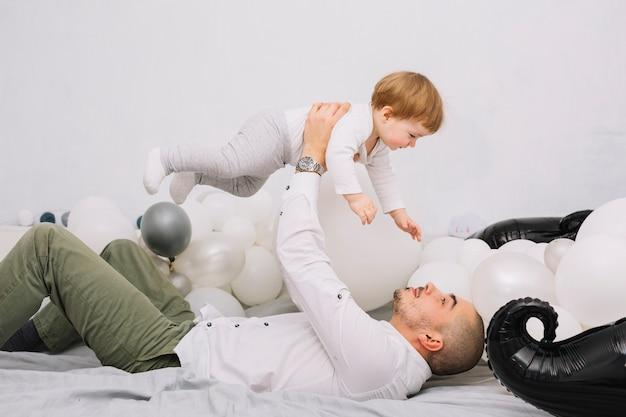 Homme montant petit bébé sur les mains et allongé sur le lit Photo gratuit