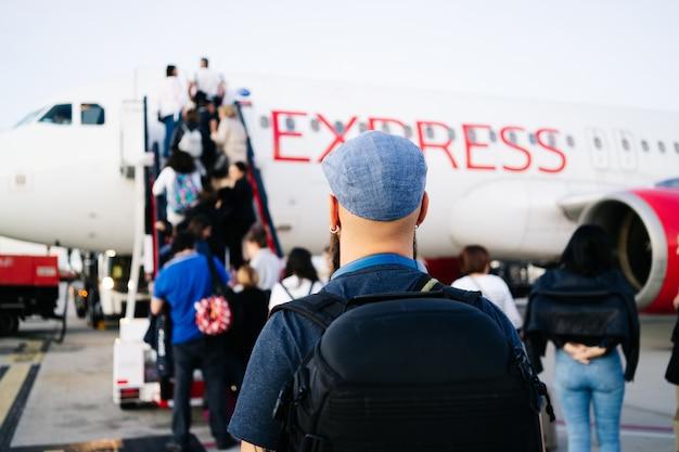 Un homme monte dans l'avion depuis la piste en bas des escaliers Photo Premium
