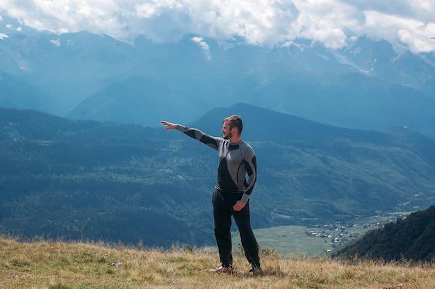 Homme Montrant La Direction Avec Sa Main Et Debout Dans Les Montagnes Photo Premium