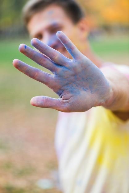 Homme montrant la main bleue à holi Photo gratuit