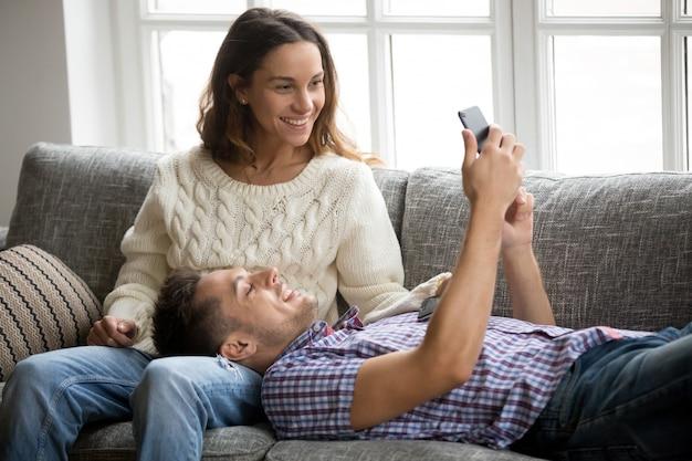Homme montrant une nouvelle application de téléphone portable pour femme se détendre sur un canapé Photo gratuit