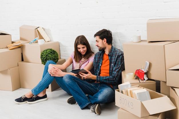 Homme montrant une tablette numérique à sa femme assise entre les piles de boîtes en carton Photo gratuit