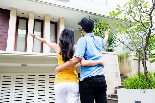 Un homme montre à sa femme leur nouvelle maison asiatique Photo Premium