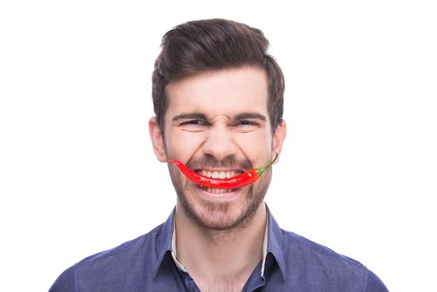 Un homme mord un piment rouge et se penche. Photo Premium