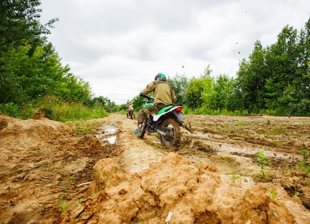 L'homme à moto roule dans la boue Photo Premium