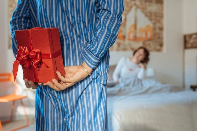 Homme Mûr Sur Son Pyjama Donnant Un Cadeau Surprise Le Jour De La Saint-valentin à Sa Femme Détendue à La Maison Au Lit Photo Premium