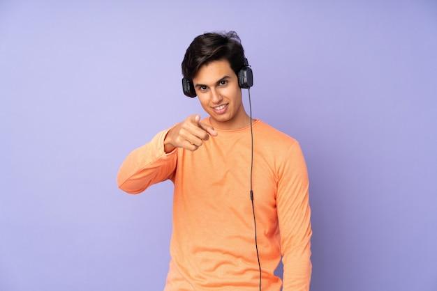 Homme Sur Mur Violet écouter De La Musique Et Pointant Vers L'avant Photo Premium