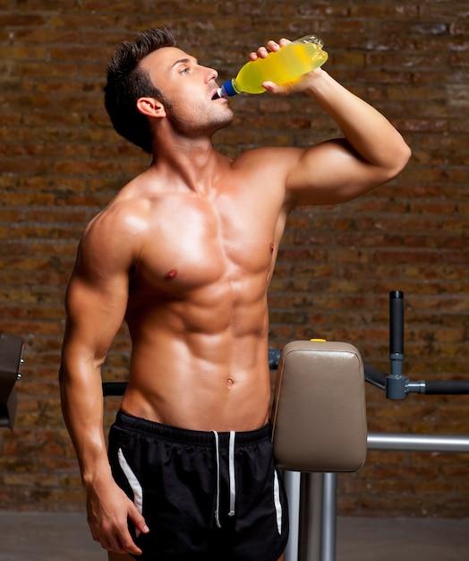 Homme muscle au gymnase détendu avec boisson énergétique Photo Premium