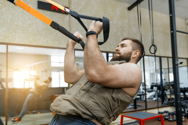 Homme musclé barbu vêtu d'un gilet blindé militaire faisant des exercices Photo Premium