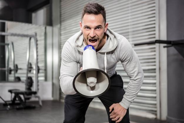 Homme musclé criant sur un mégaphone à la salle de gym crossfit Photo Premium