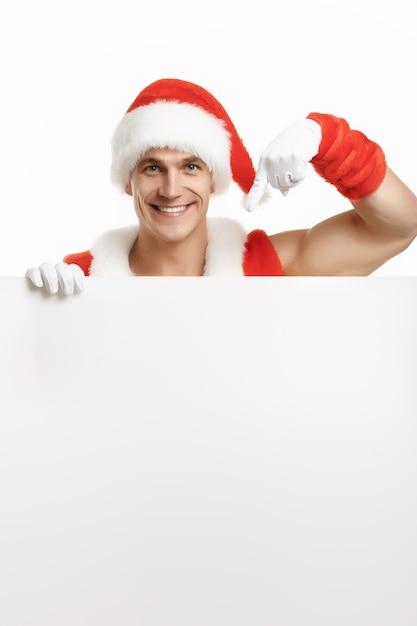 Homme musclé déguisé en père noël pointant vers un panneau blanc en souriant Photo gratuit