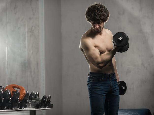 Homme musclé entraîne des haltères biceps dans la salle de sport, entraînement de la main Photo Premium