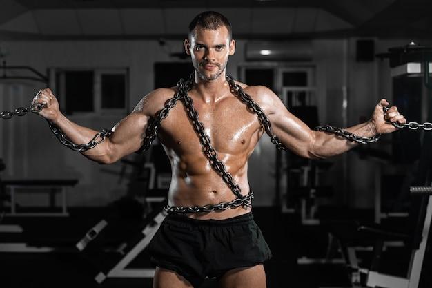 Homme musclé esclave enchaîné au gymnase, le prisonnier Photo Premium