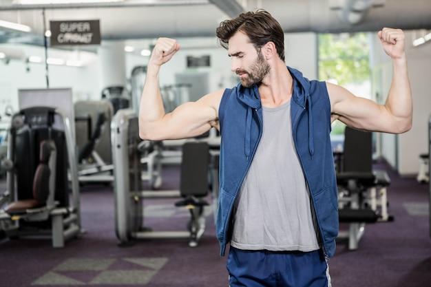 Homme musclé montrant les biceps au gymnase Photo Premium