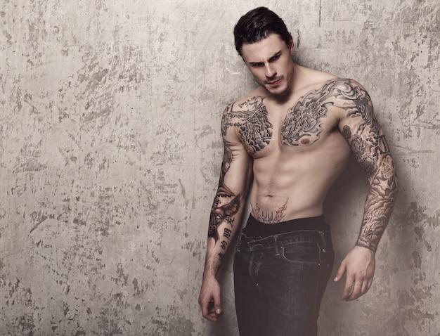 Homme musclé avec tatouage Photo gratuit