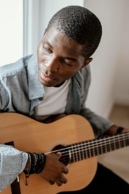 Homme Musicien Jouant De La Guitare Sur Le Lit Photo gratuit