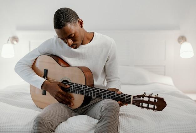 Homme Musicien Sur Le Lit à Jouer De La Guitare Photo gratuit