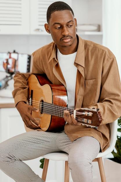 Homme Musicien à La Maison Sur Une Chaise Jouant De La Guitare Et Enregistrement Avec Smartphone Photo gratuit