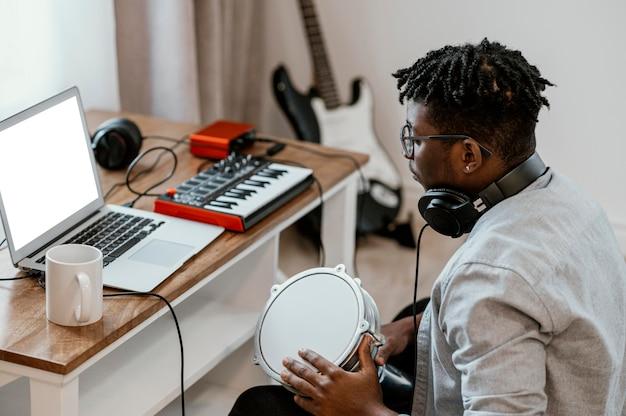 Homme Musicien à La Maison à Jouer De La Batterie Et à Mélanger Avec Un Ordinateur Portable Photo gratuit