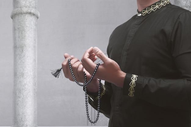 Homme musulman priant avec des perles de prière Photo Premium