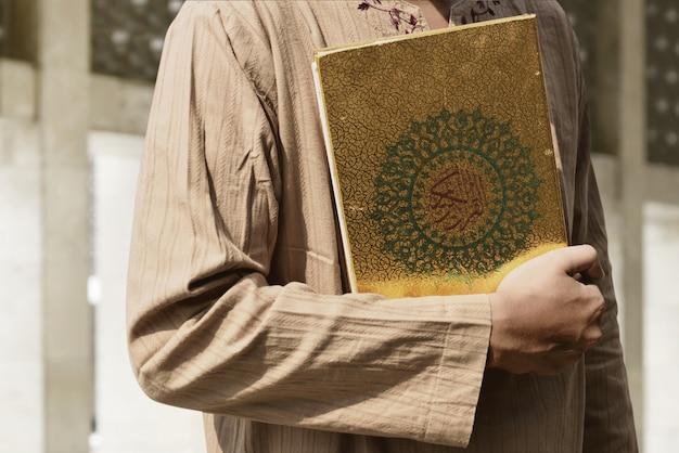 Homme musulman tenant le coran Photo Premium