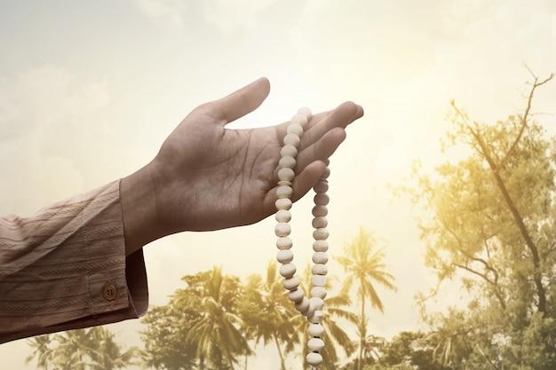 Homme musulman tenant des perles de prière Photo Premium
