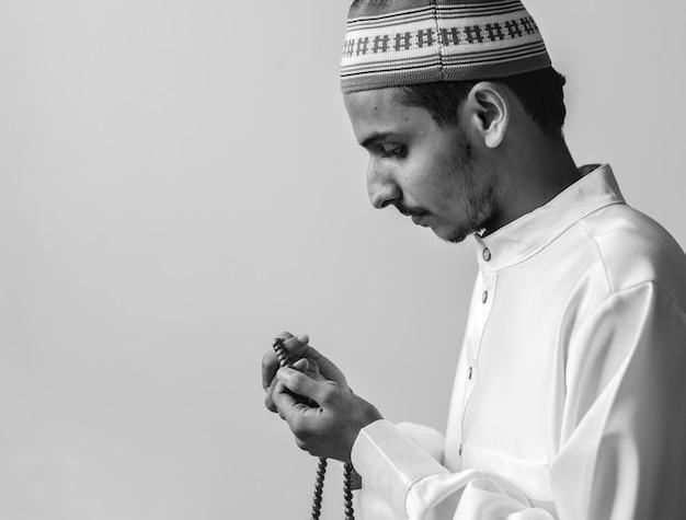 Homme musulman utilisant la misbaha pour garder une trace de son compte à tasbih Photo gratuit