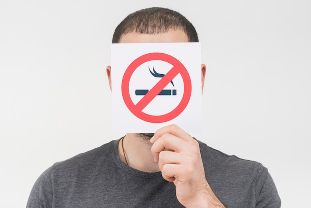 Un homme ne tenant aucun signe de fumer devant son visage sur fond blanc Photo gratuit