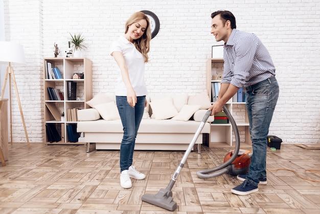 Un homme nettoyant un aspirateur dans la chambre d'une femme. Photo Premium