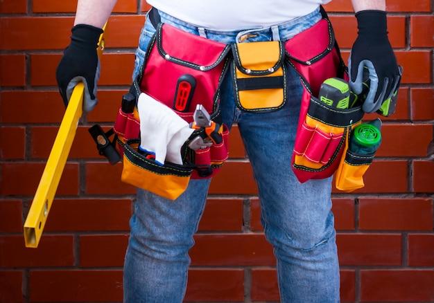 Un homme avec un niveau debout dans la main sur le fond d'un mur de briques rouges avec un sac à outils complet. Photo Premium