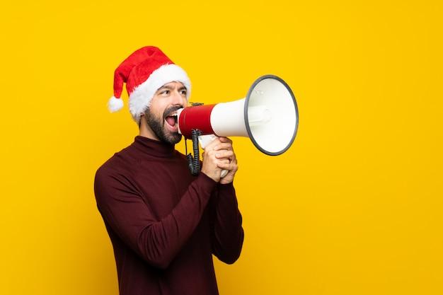 Homme, à, noël chapeau, sur, isolé, jaune, mur, crier, par, a, mégaphone Photo Premium
