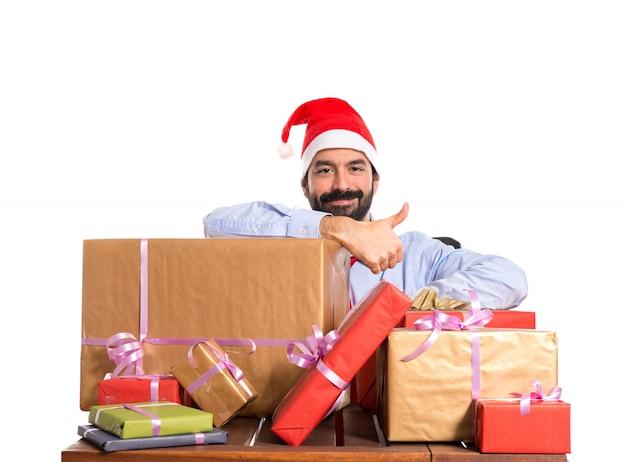 Homme de noël dans son bureau avec plusieurs cadeaux Photo gratuit