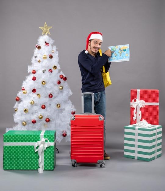 Homme De Noël Excité Avec Sac à Dos Jaune Vérifiant Une Carte Près De L'arbre De Noël Sur Fond Gris Photo gratuit