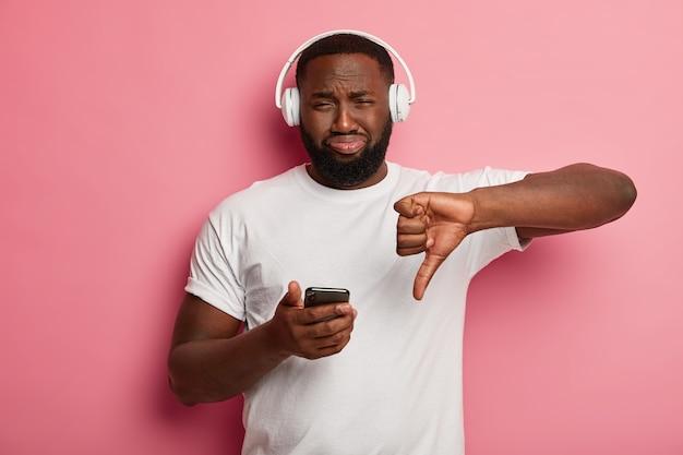 Un Homme Noir Barbu Mécontent N'aime Pas Le Geste, N'aime Pas La Chanson De La Liste De Lecture, Entend La Bande Sonore Dans Les écouteurs Photo gratuit