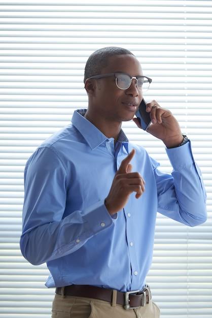 Homme noir faisant un appel téléphonique contre la fenêtre à volets Photo gratuit