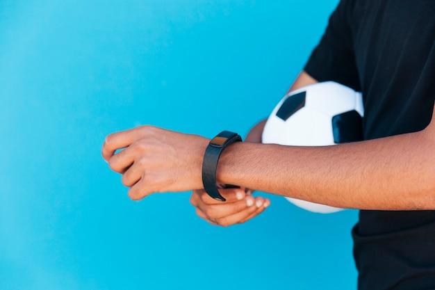 Homme noir avec le football fixant une montre intelligente Photo gratuit