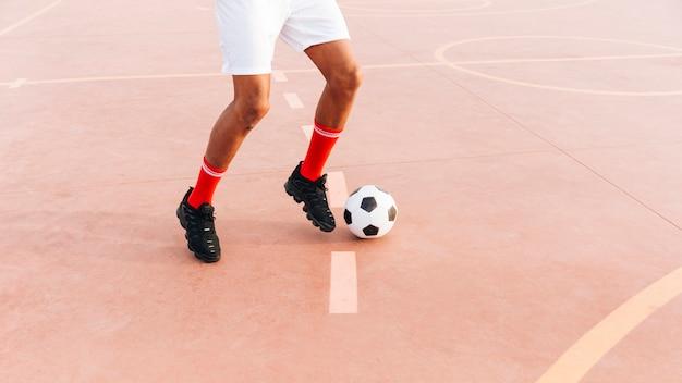 Homme noir jouant au football au stade Photo gratuit