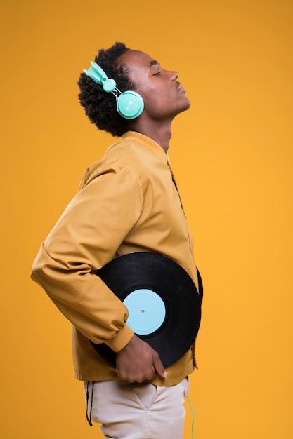 Homme noir posant avec des vinyles Photo gratuit