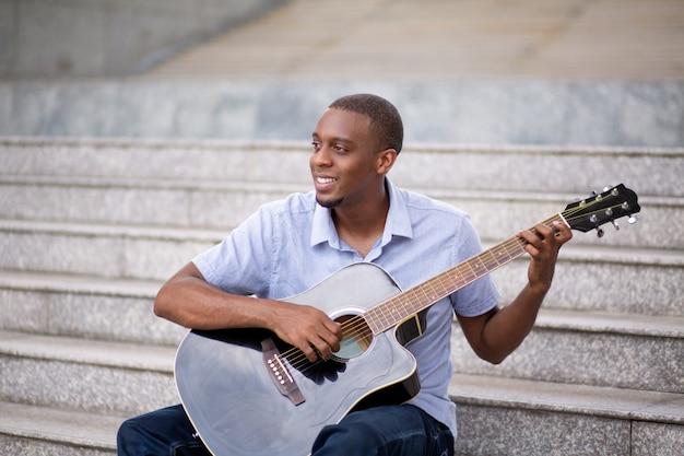 Homme noir souriant jouant de la guitare et assis dans les escaliers Photo gratuit