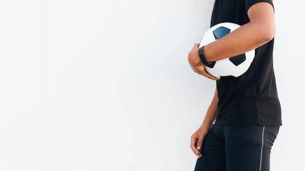 Homme noir en tenue de sport avec ballon de foot Photo gratuit