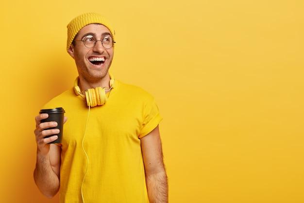 L'homme Optimiste Dans Des Verres Rit Comme Passe Du Temps Avec Des Amis Pendant La Pause-café, Tient Une Tasse Jetable, Regarde Ailleurs Photo gratuit