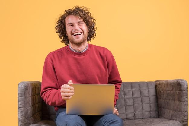 Homme avec ordinateur portable sur le canapé Photo gratuit